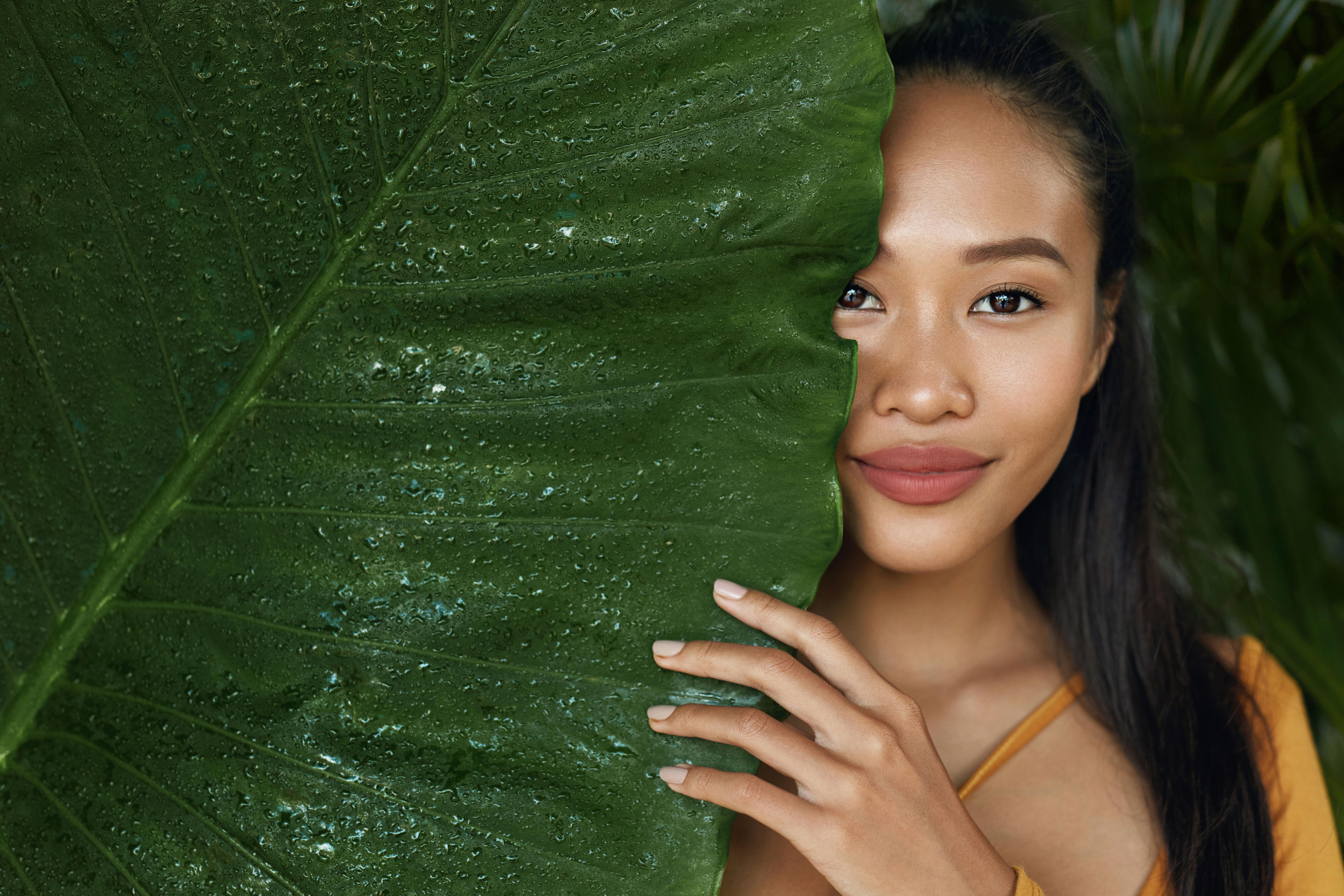 A girl next to a large fern leaf