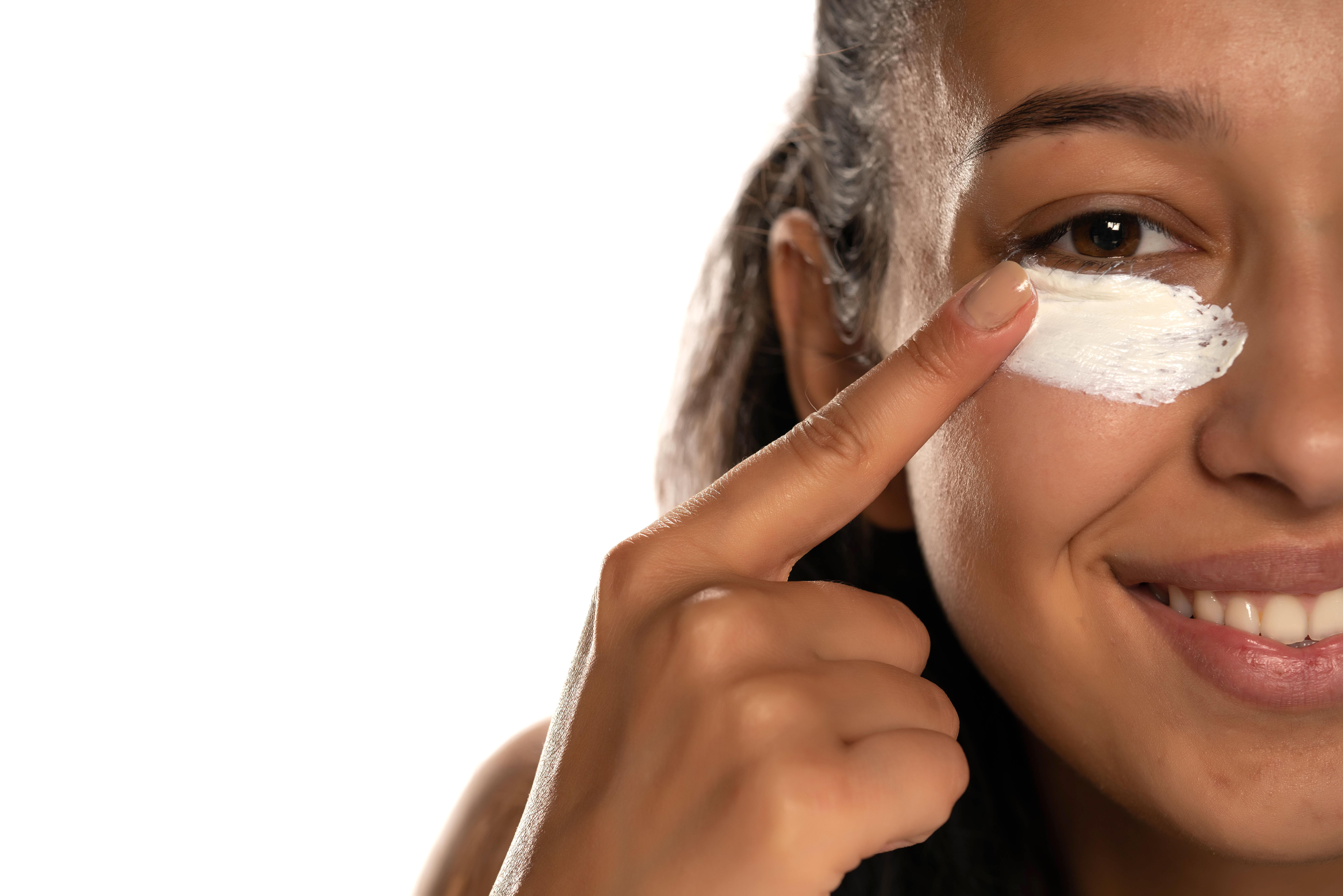 The girl uses cream under the eye