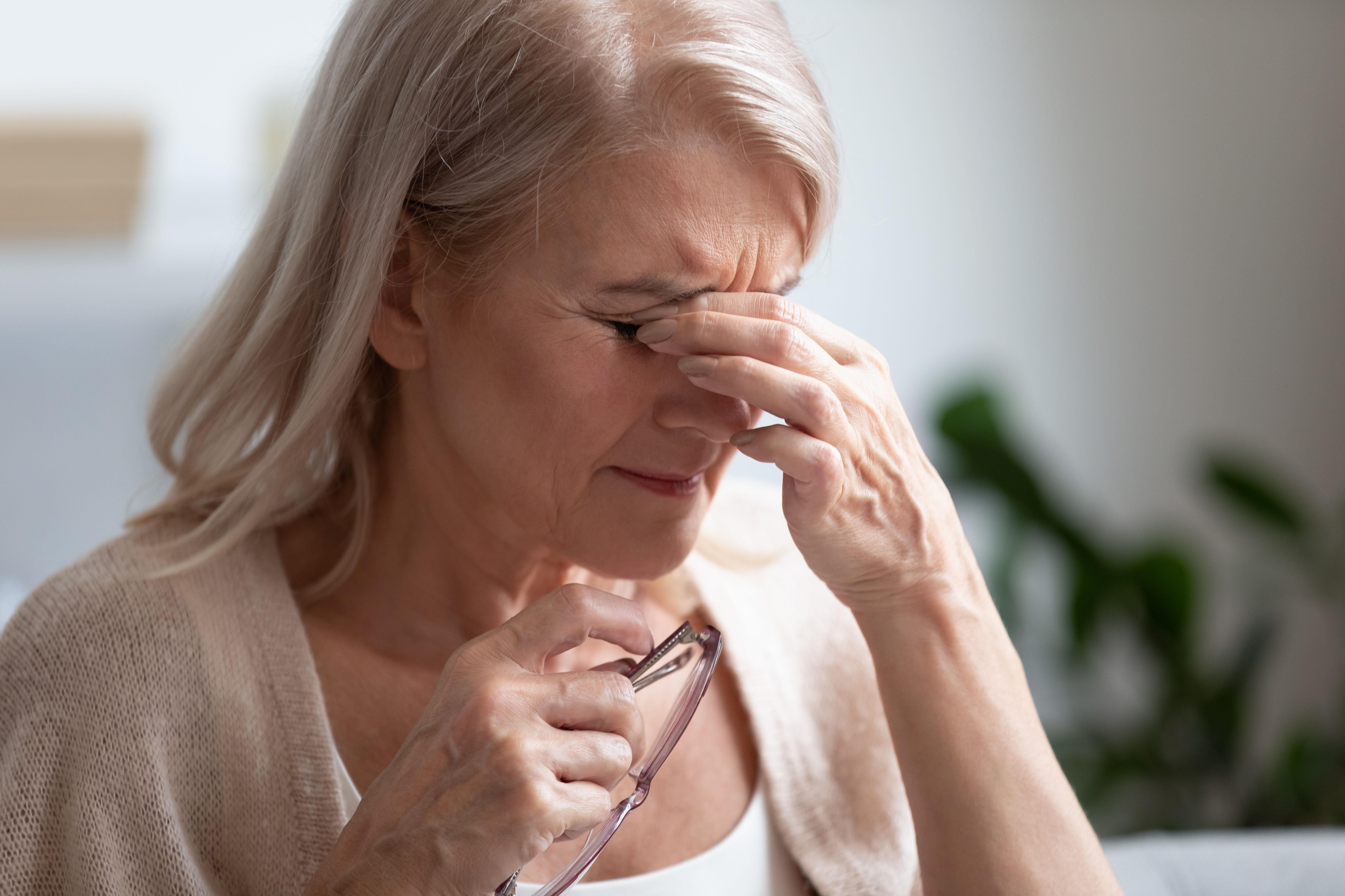 Woman rubs tired eyes