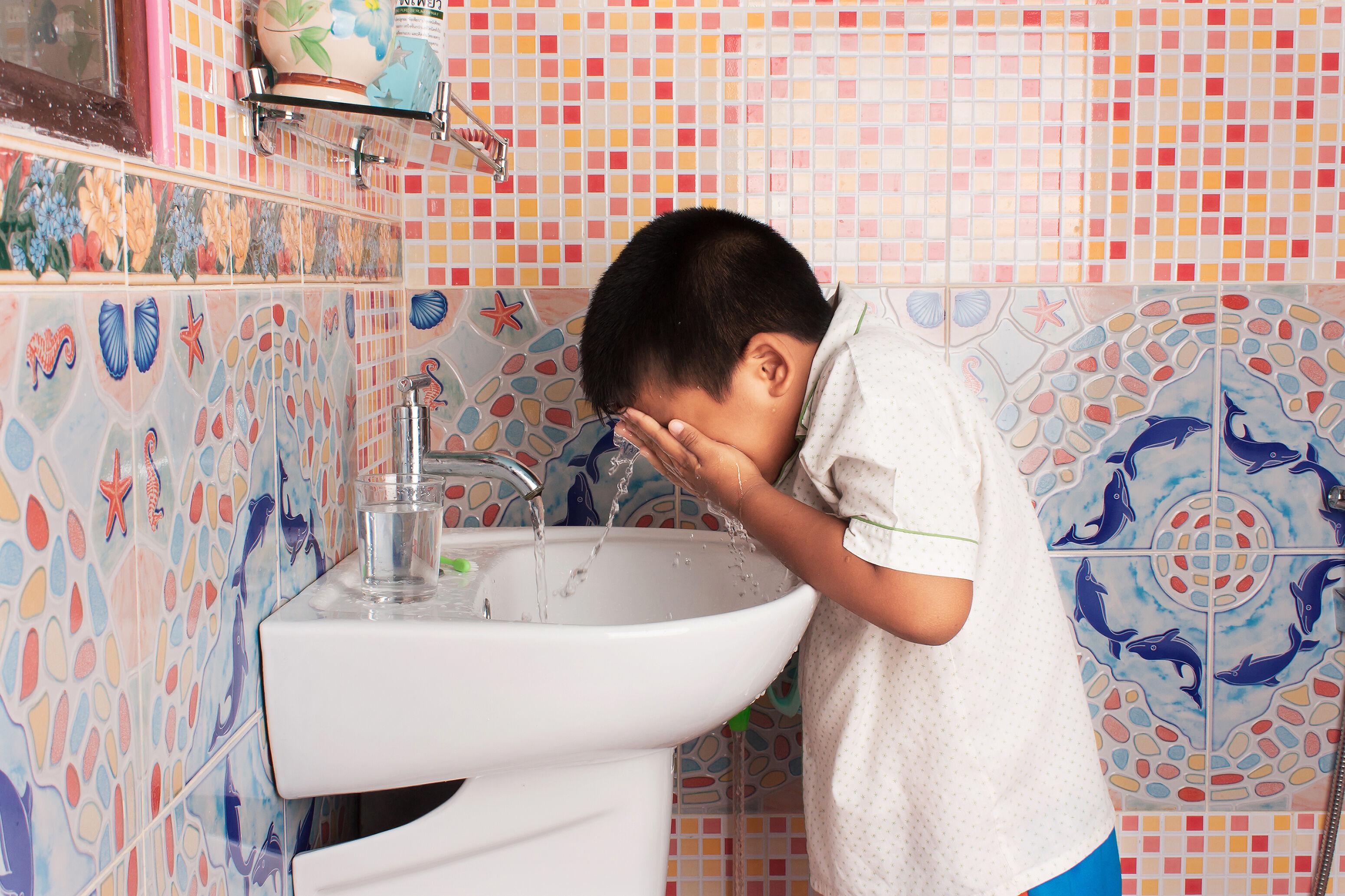 Boy washes his eyes