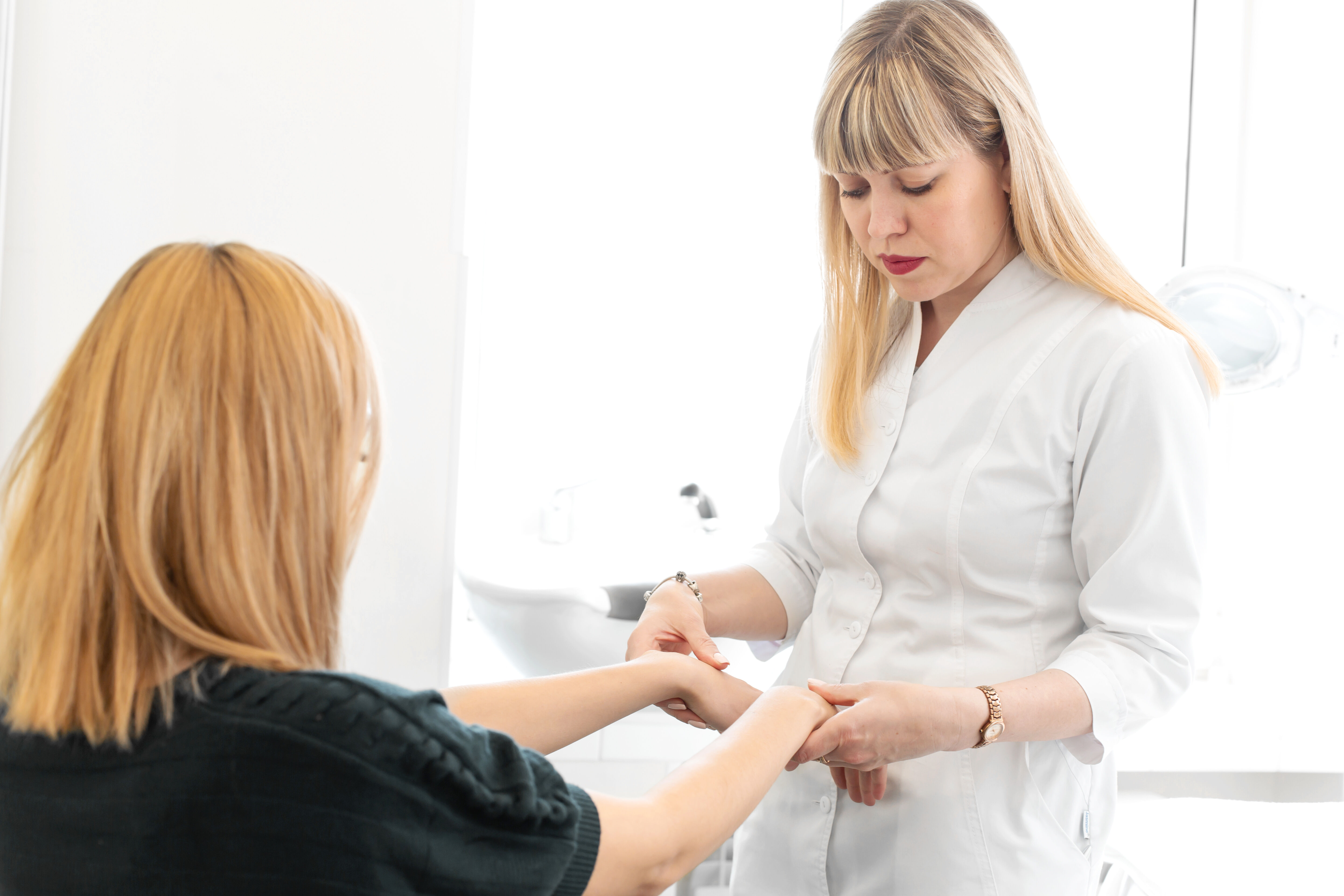 Dermatologist looks at the hands of the patient