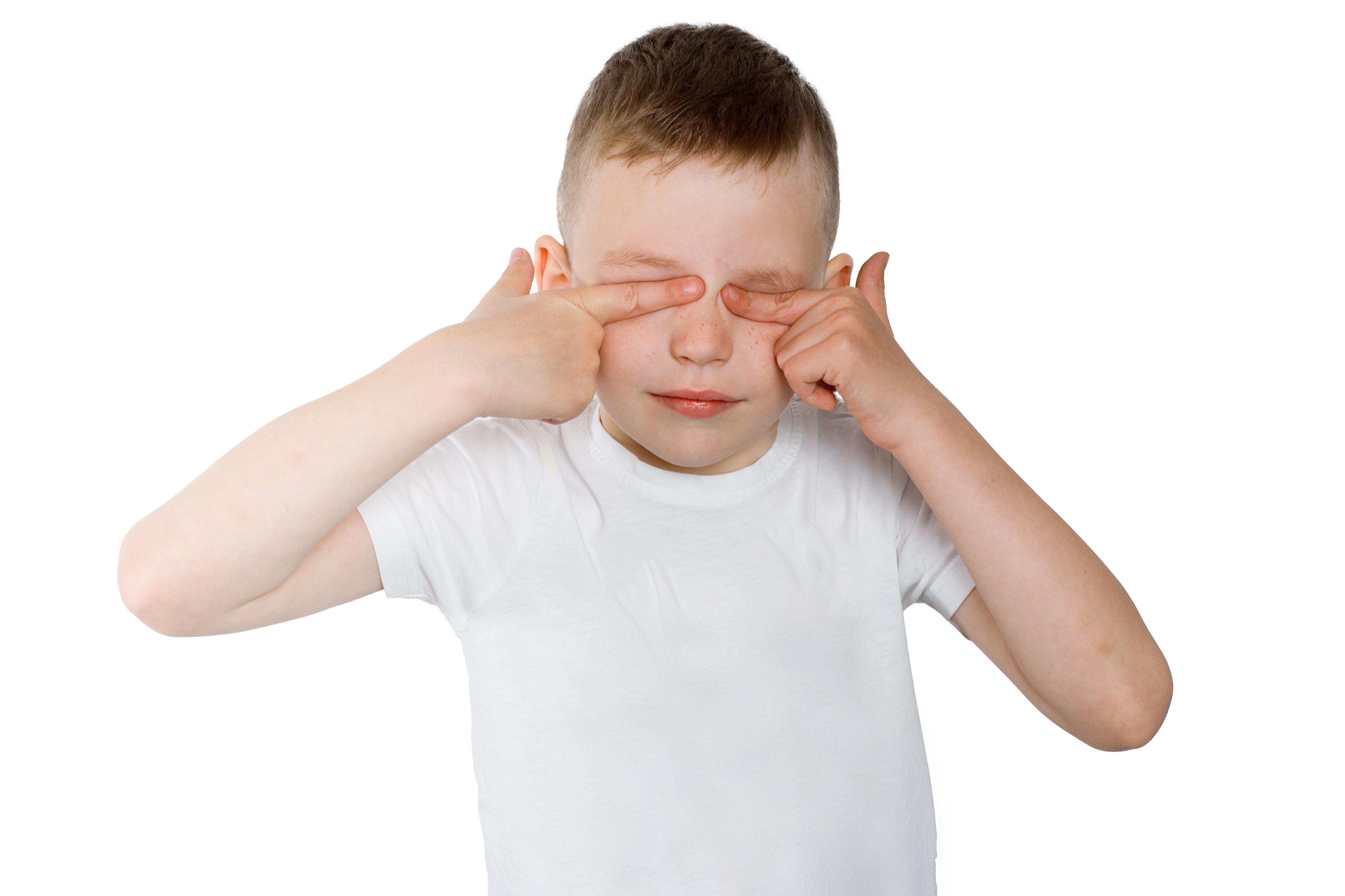 Boy rubs his eyes