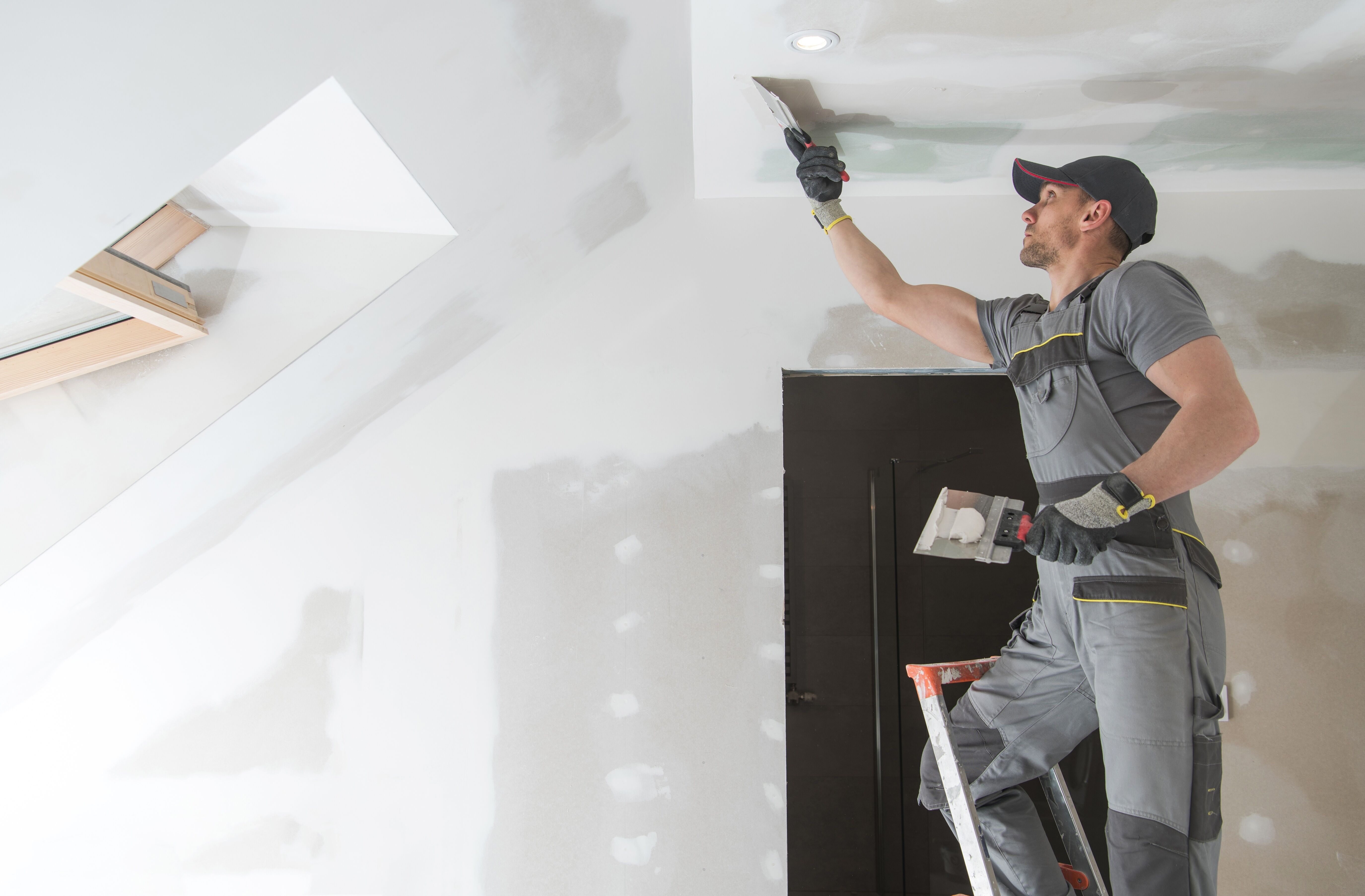 Worker putties the ceiling
