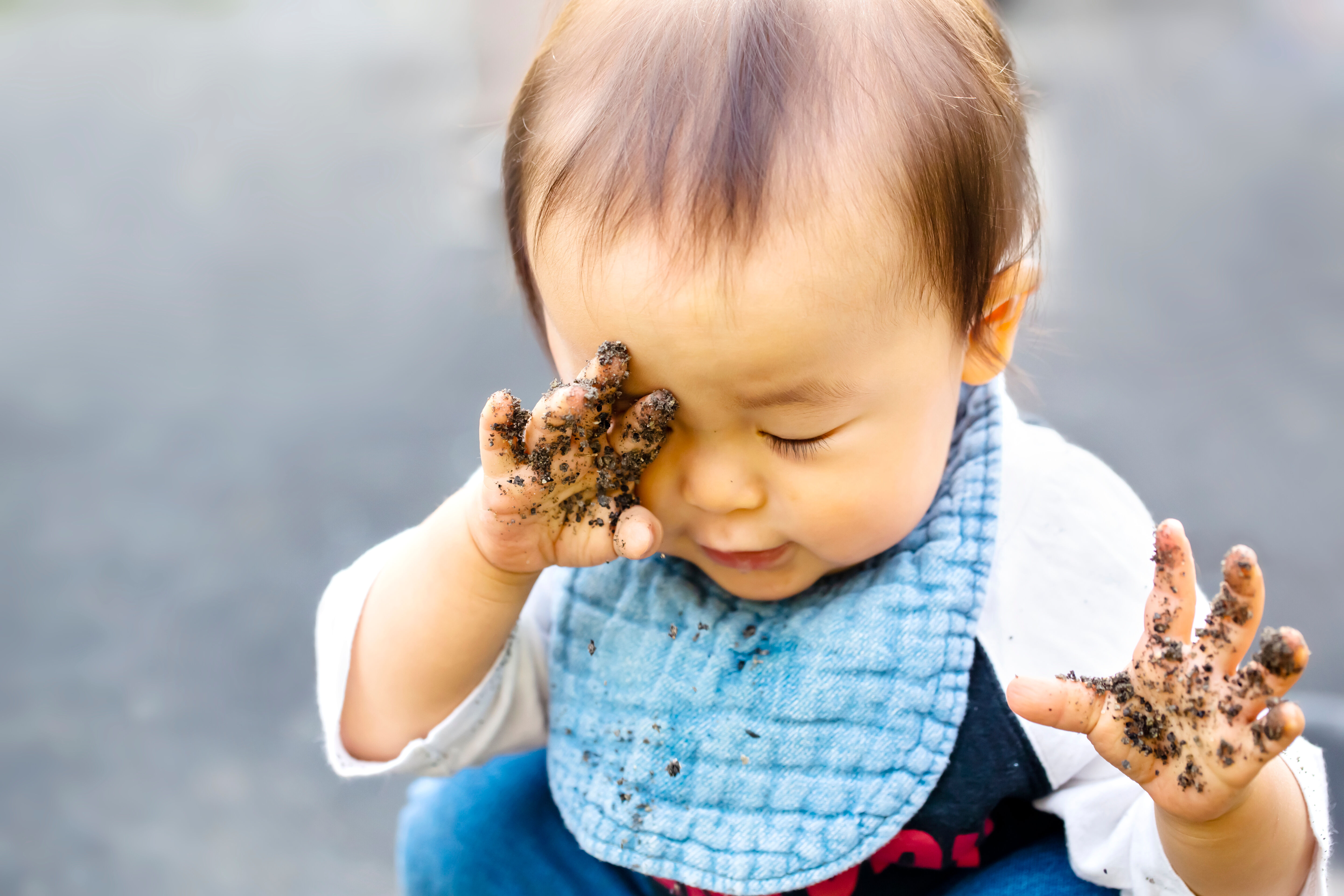 Child rubs eyes with dirty hands
